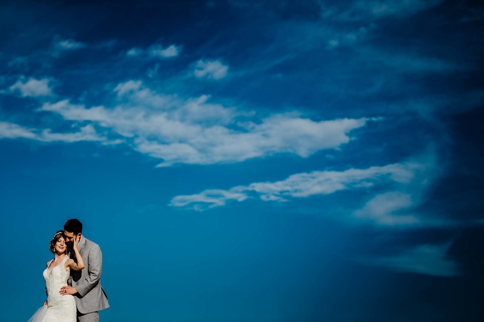 bride and groom portrait with blu sky