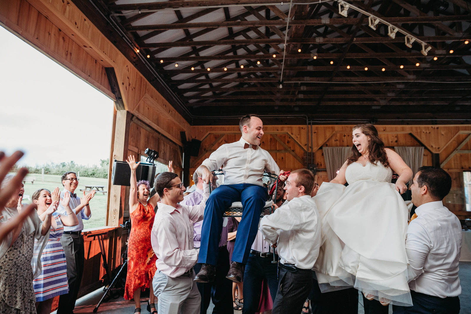 bride and groom raised in air on chairs during jewish wedding in massachusetts