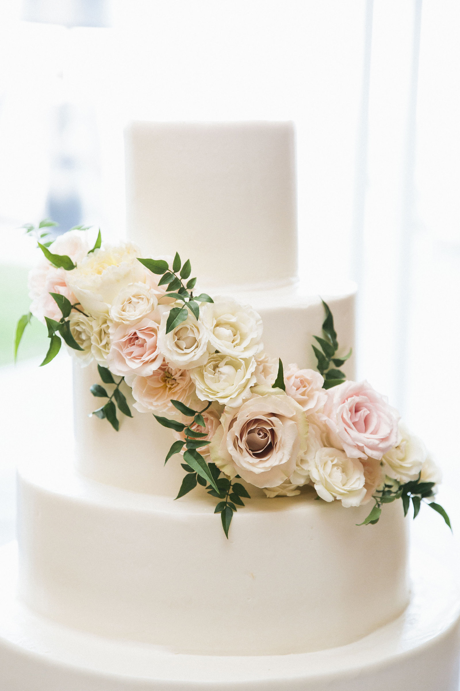 Wedding cake with florals on the tiers by Montilio's bakery