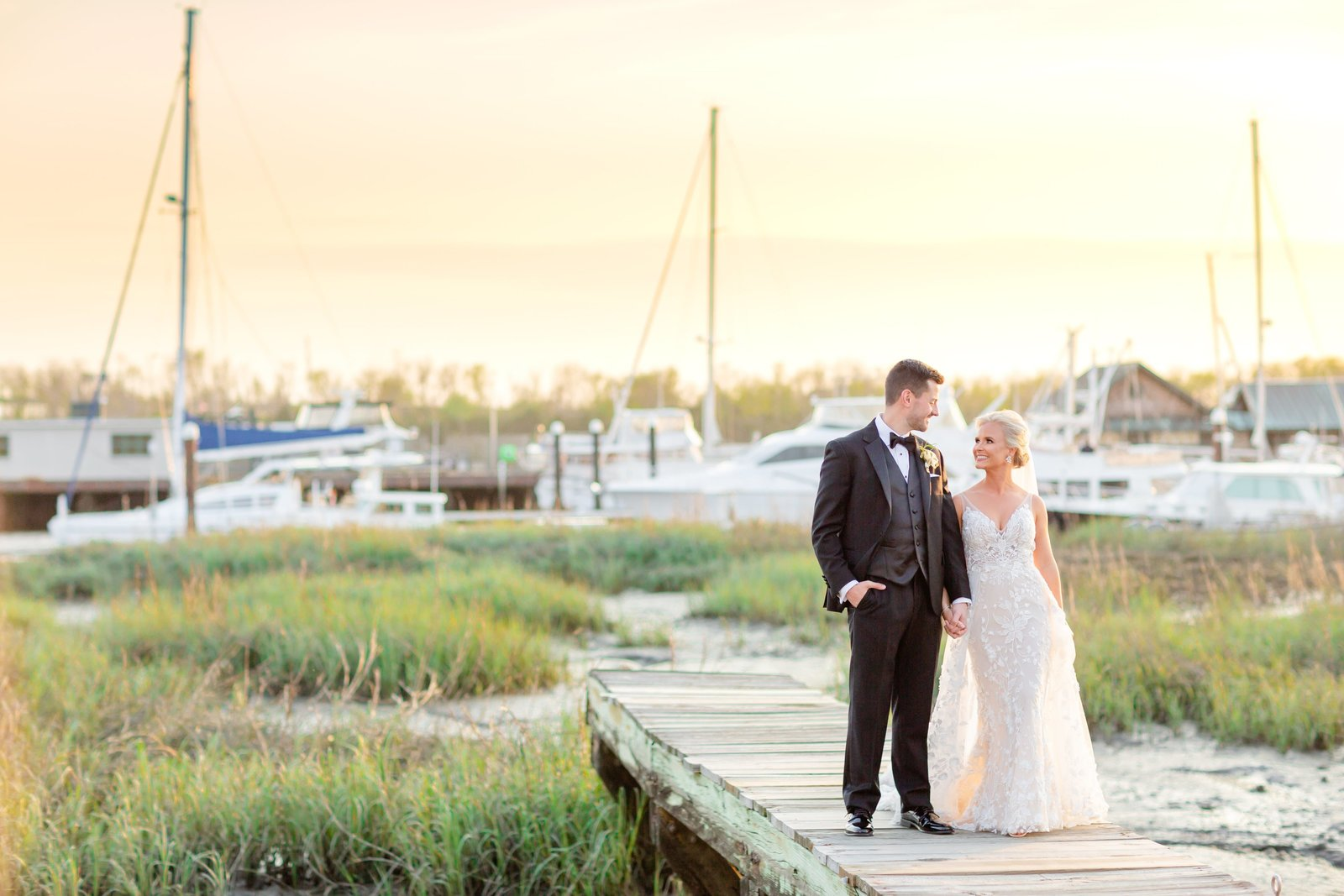 The Historic Rice Mill wedding - couple poses on the dock with the charleston harbor behind them and a stunning sunset is staining the sky