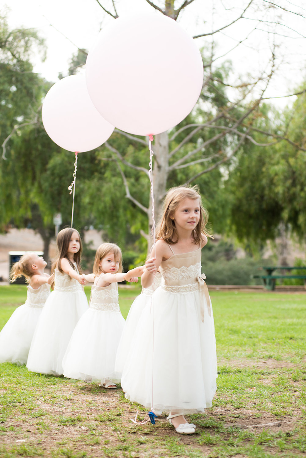 Flower girls make their entrance at an outdoor wedding ceremony