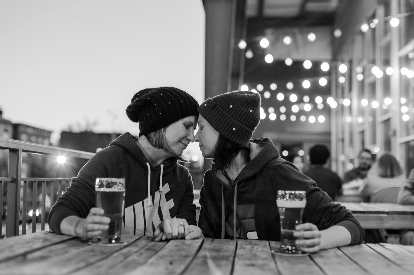 Black and white engagement photo of a lesbian couple drinking beer at Urban Chestnut Brewing in St. Louis
