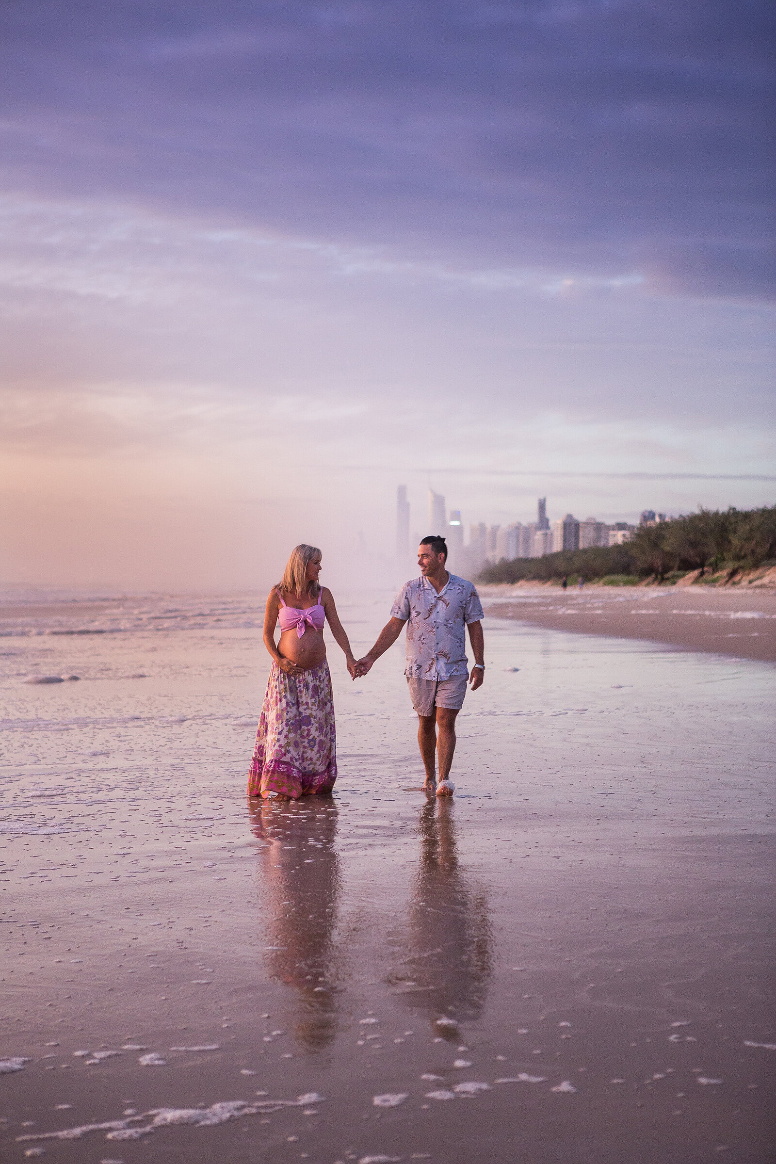 Professional maternity portrait of couple holding hands on Gold Coast beach