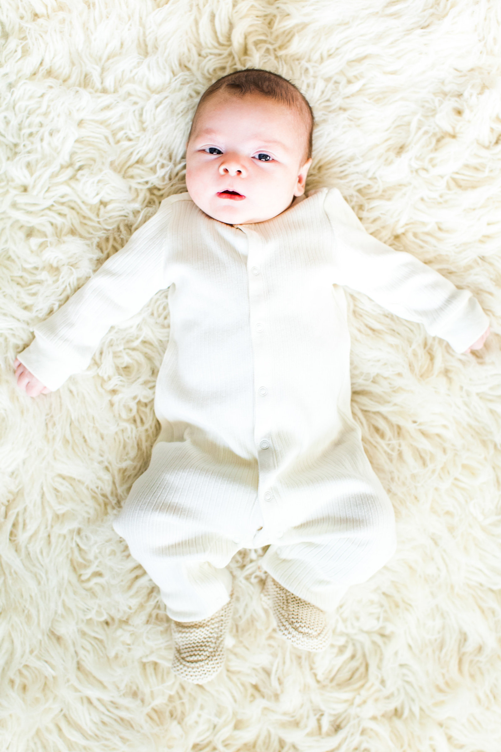 Newborn on faux fur rug in all white