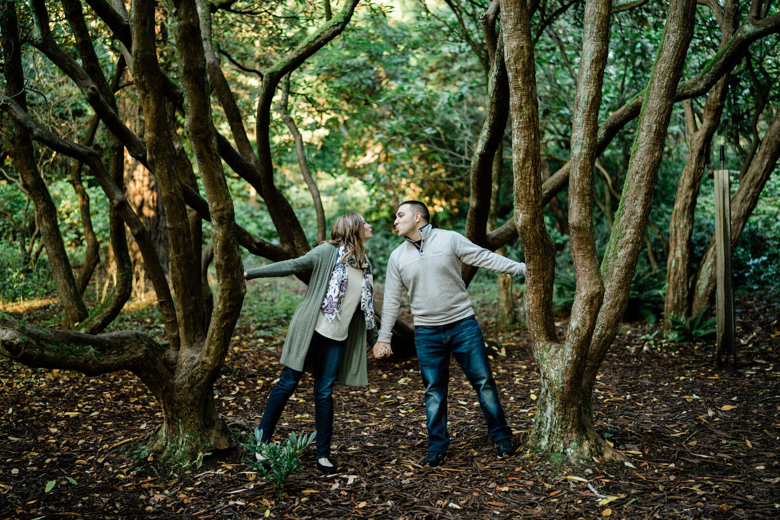 creative engagement photos in seattle at university of washington arboretum as coupe holds hands near large trees