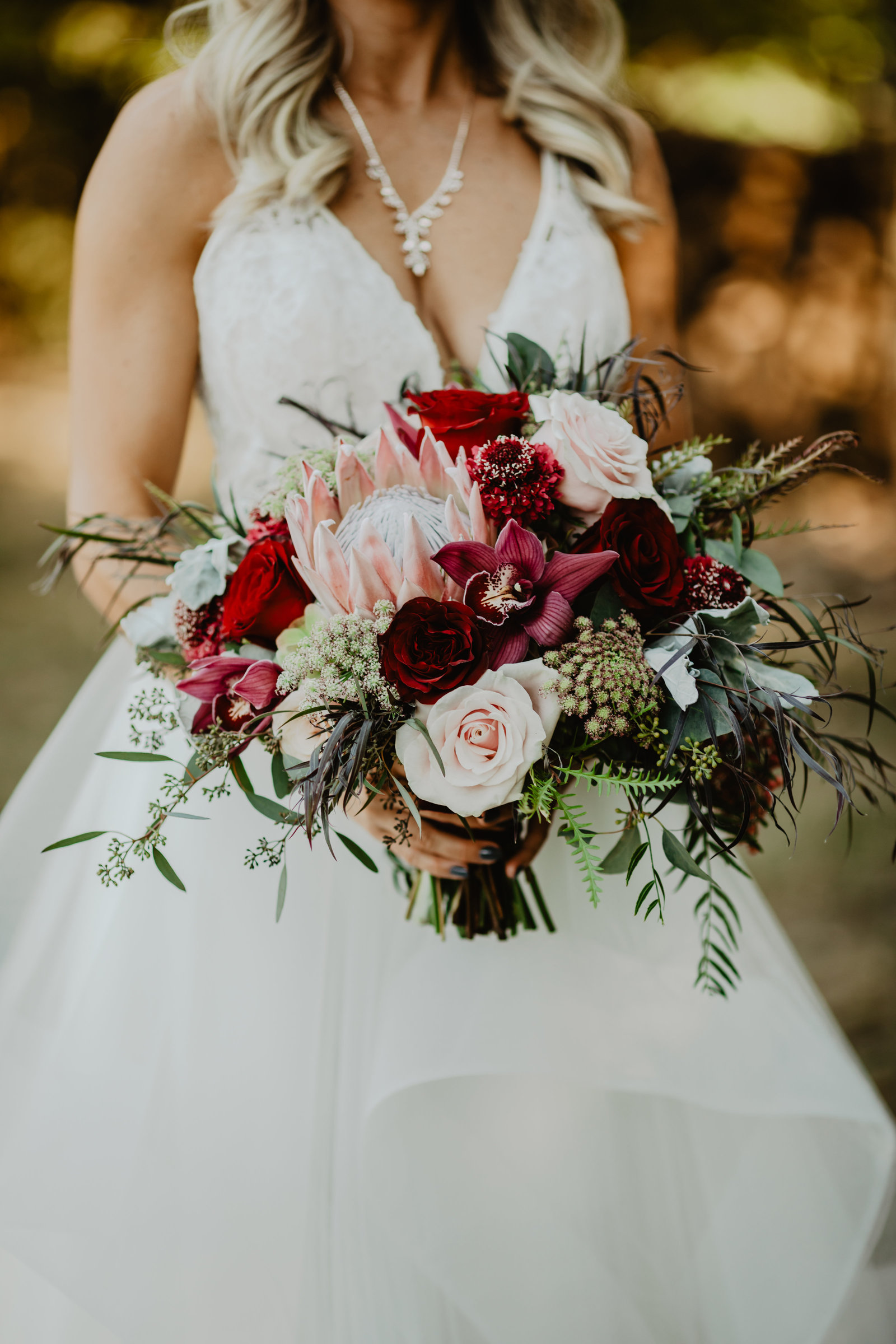 Bridal bouquet with pink and maroon accents.