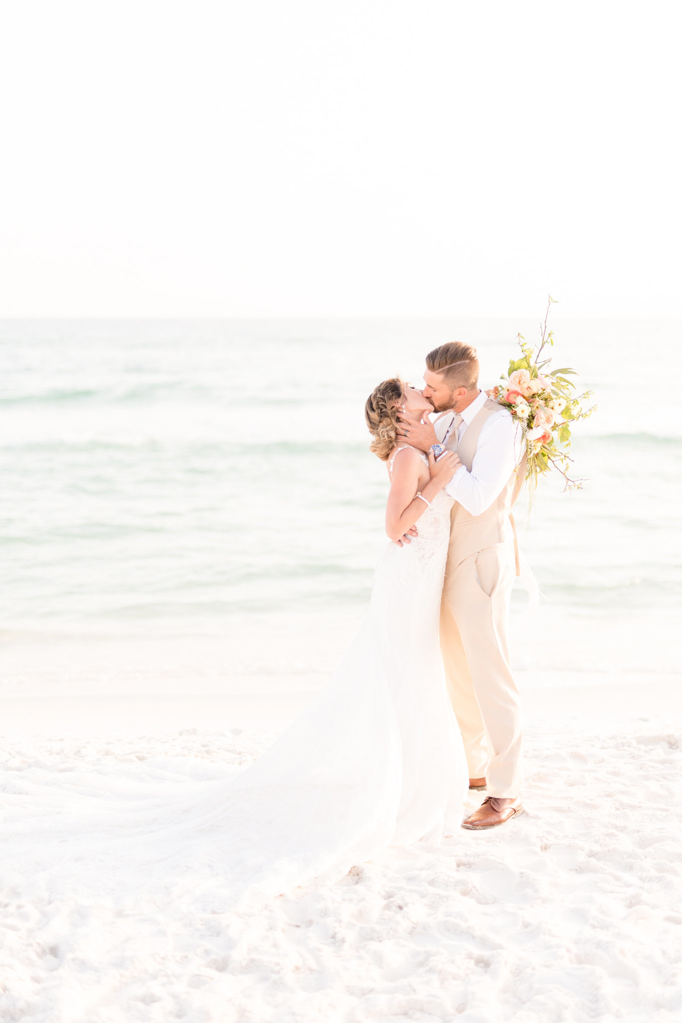 Bride and Groom kiss on beach during sunset.
