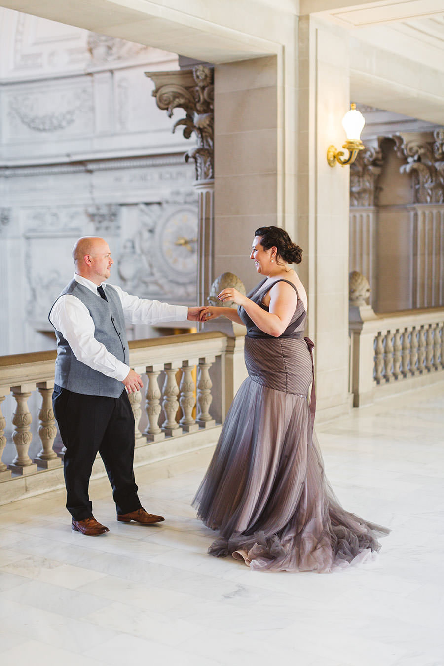 bride in gray dress being twirled by new husband after marrying at san francisco city hall