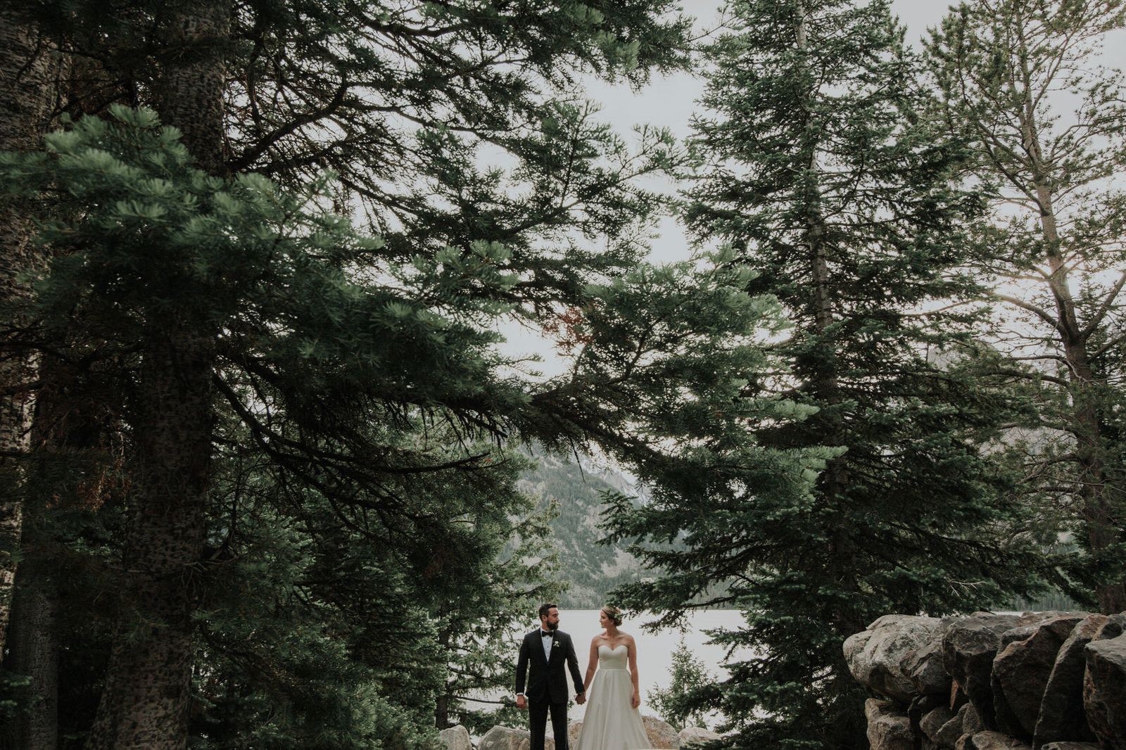 couple stands in a forrest in wyoming at their wedding