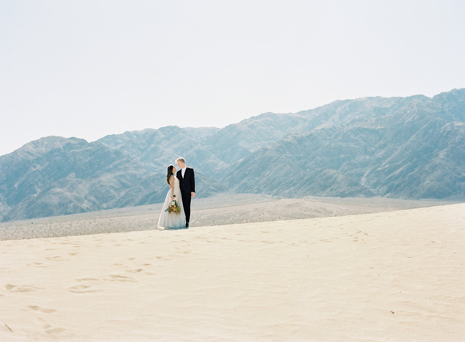 Bride and groom on sand dune in death valley Photographed by Amy Mulder Photography