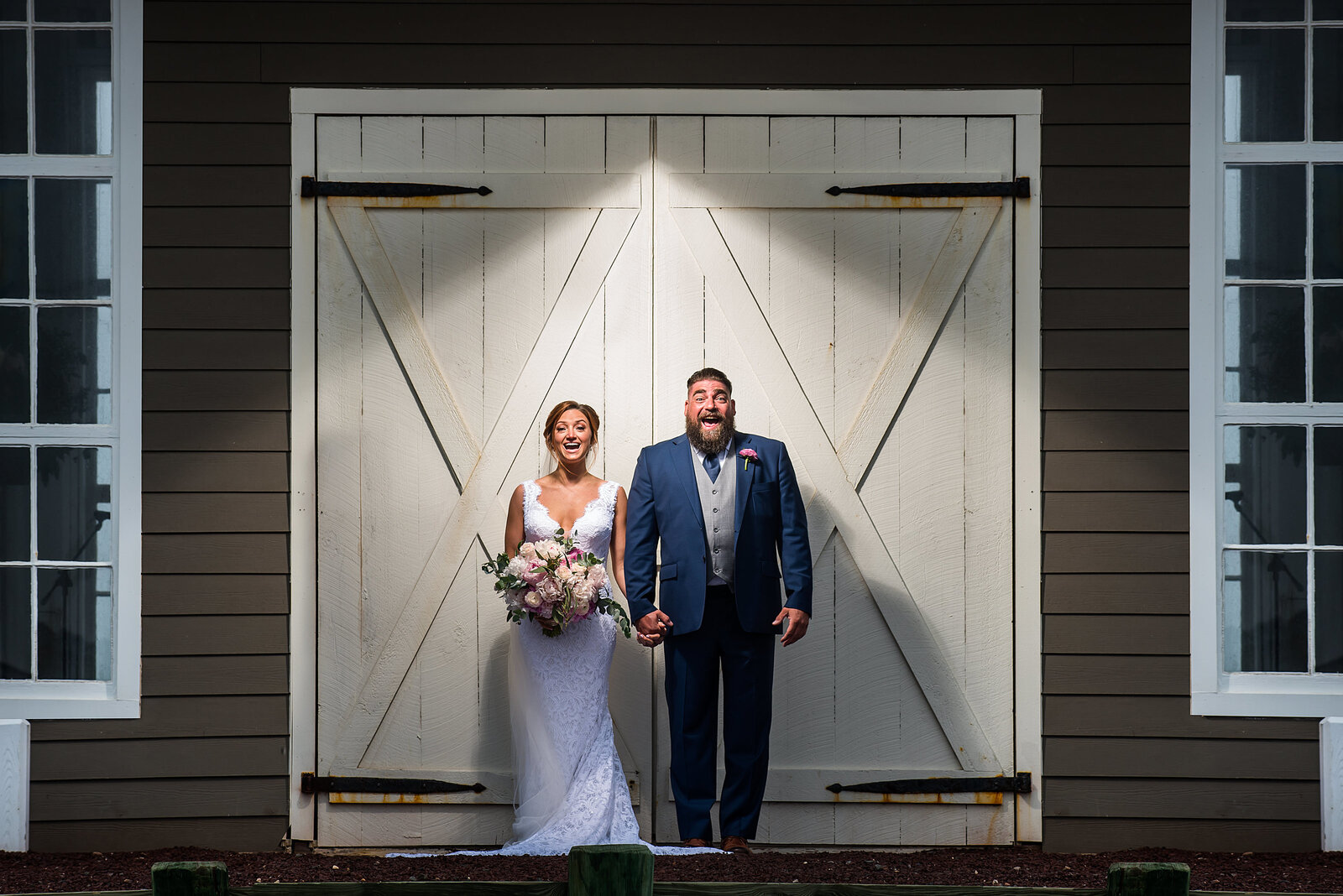 A couple stands against the bard doors of the wedding chapel at Mallard Island Yacht Club, NJ