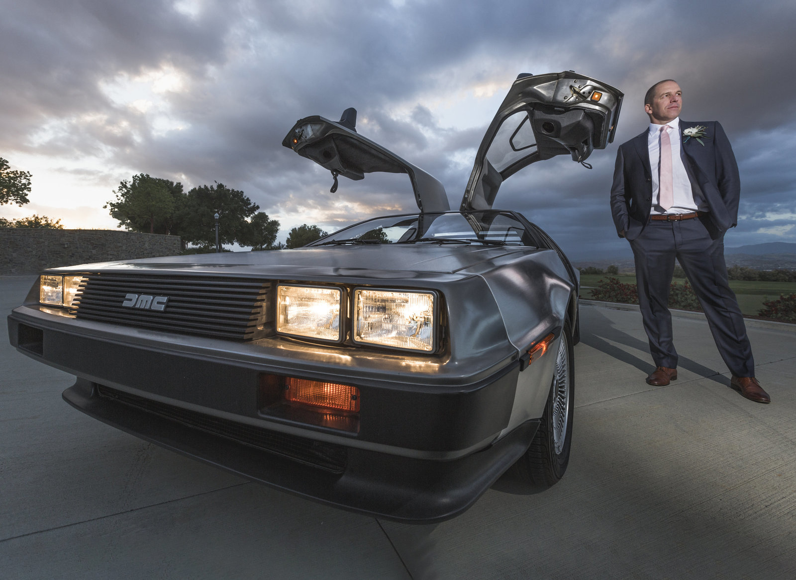 groom posing next to his gmc delorean.