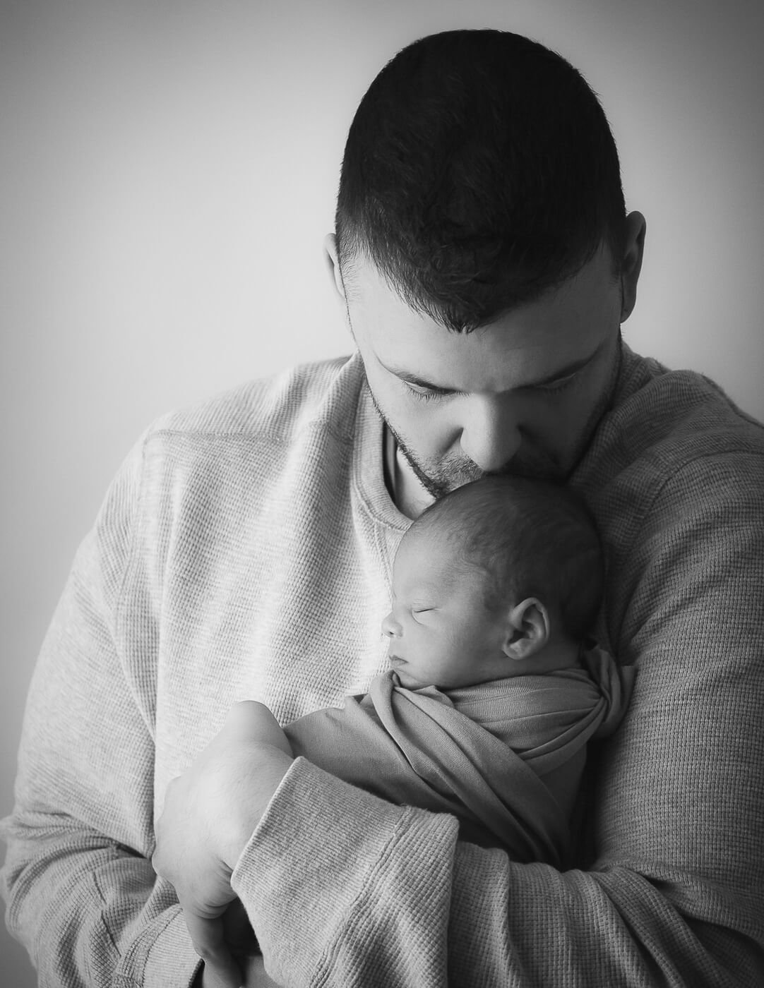 Sweet newborn boy posed with his dad in our Rochester, NY studio.
