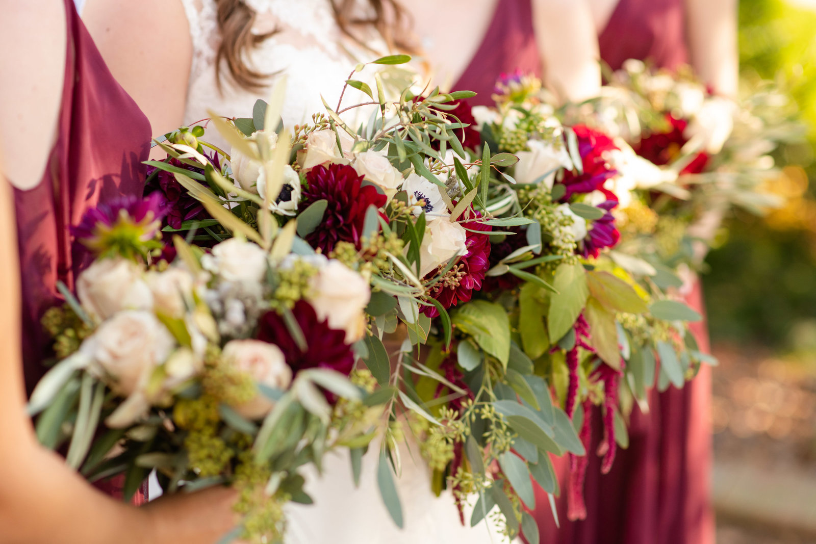 bride and bridesmaids holding bouquets with burgundy flowers
