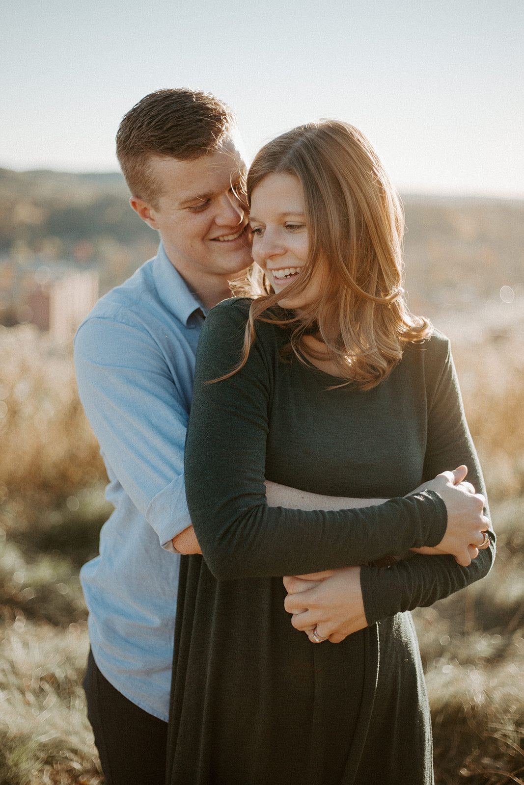 Man hugging his girlfriend form behind during their Minneapolis engagement session