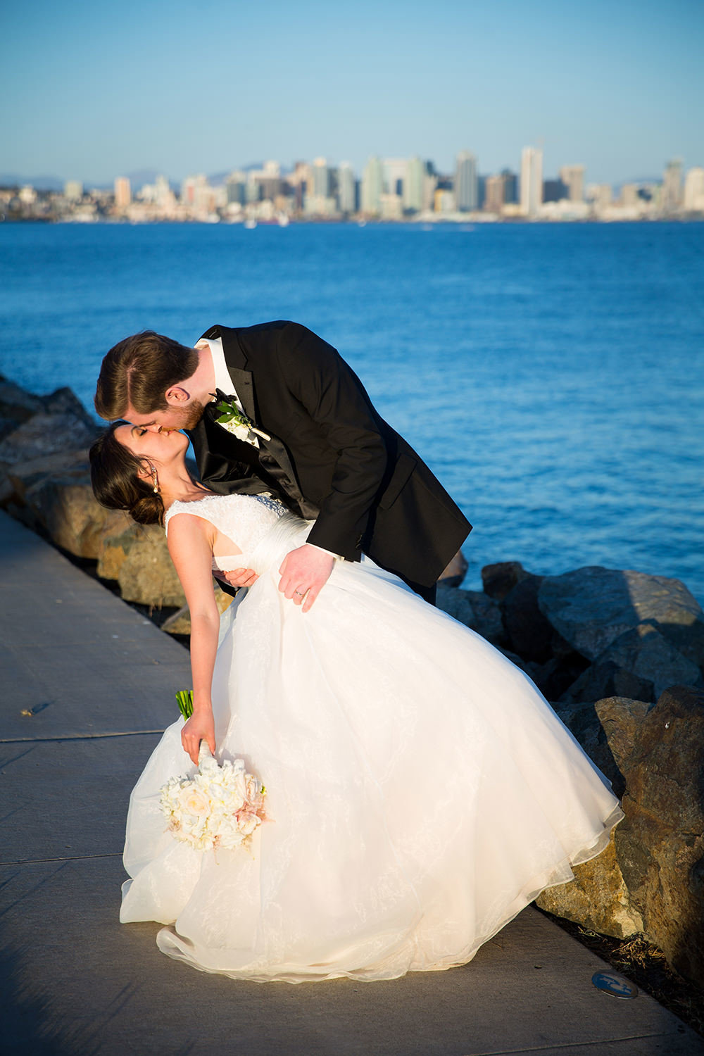 bride and groom kissing with san diego skyline