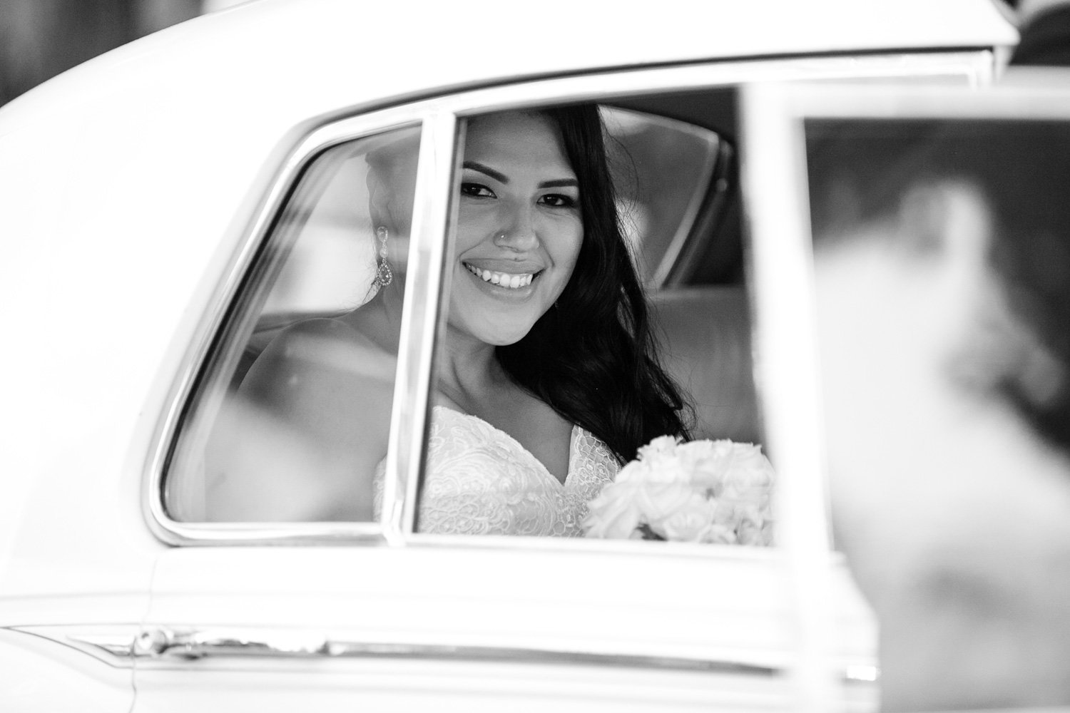 black and white photo of bride in rolls royce at wayfarers chapel