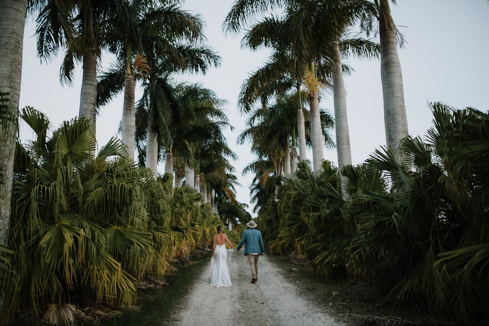 Bride and Groom walking among palms