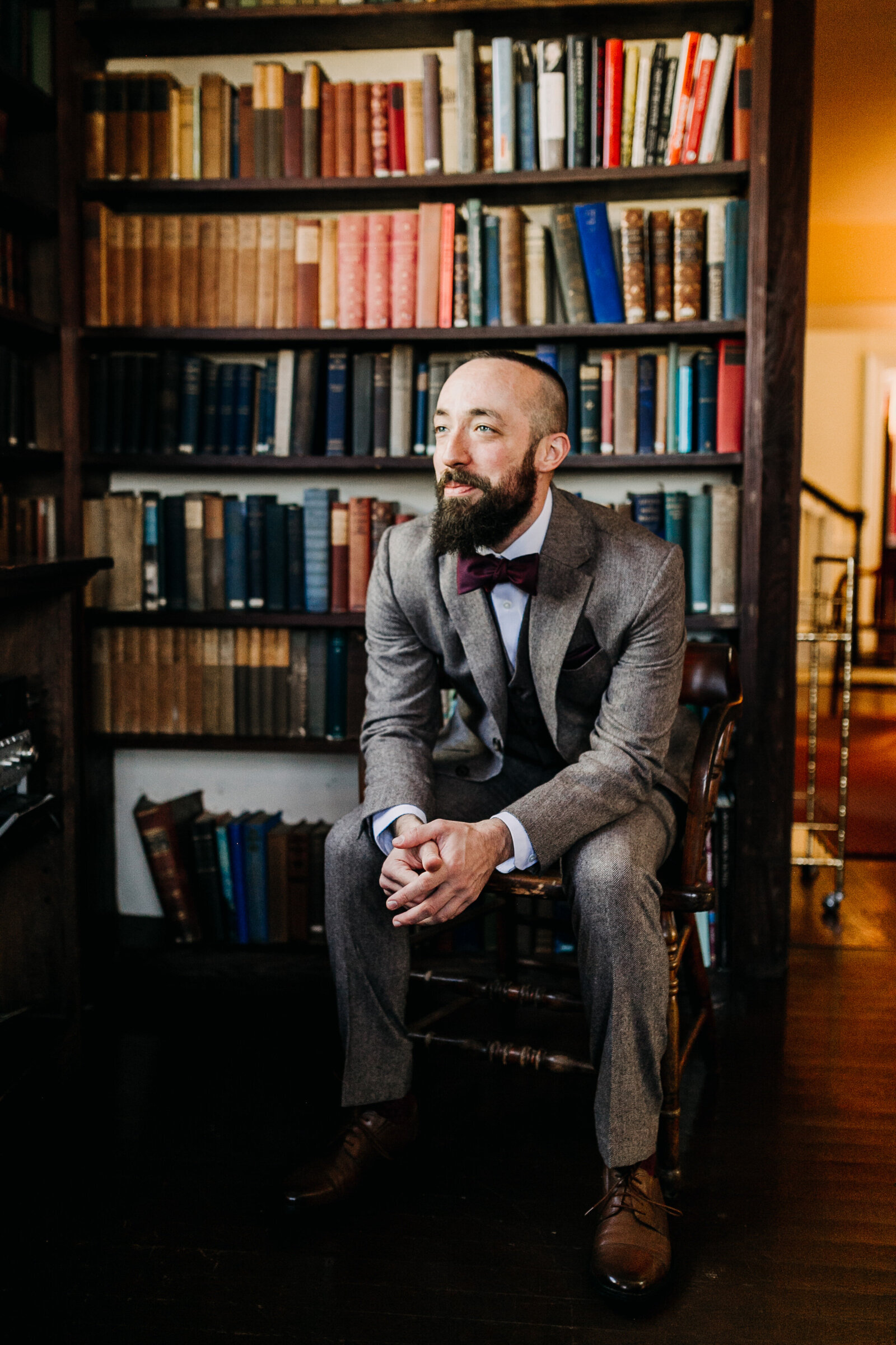 groom with bowtie wool suit in old library