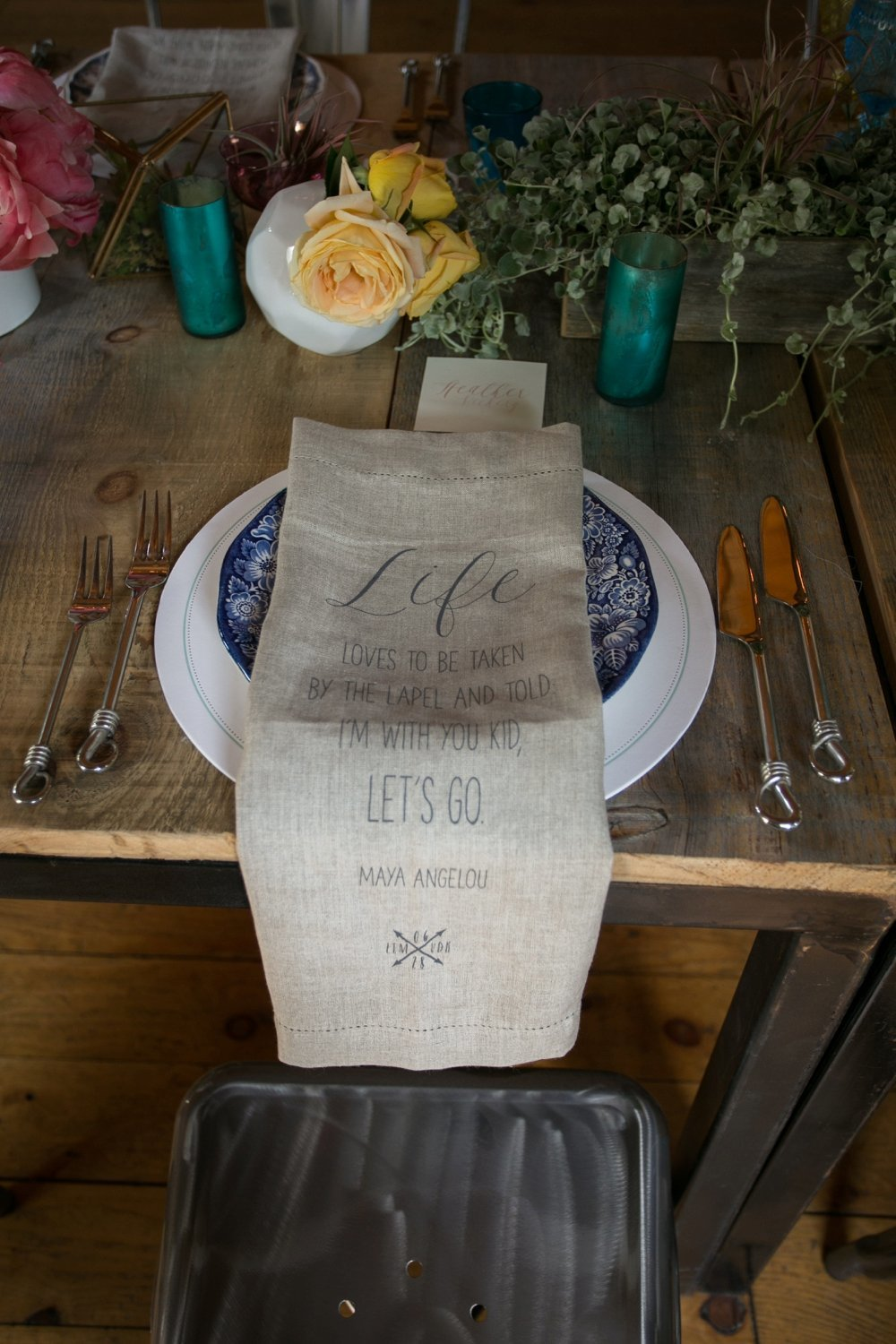 Rustic barn wedding place setting with custom linen napkins at The Barn on Walnut Hill