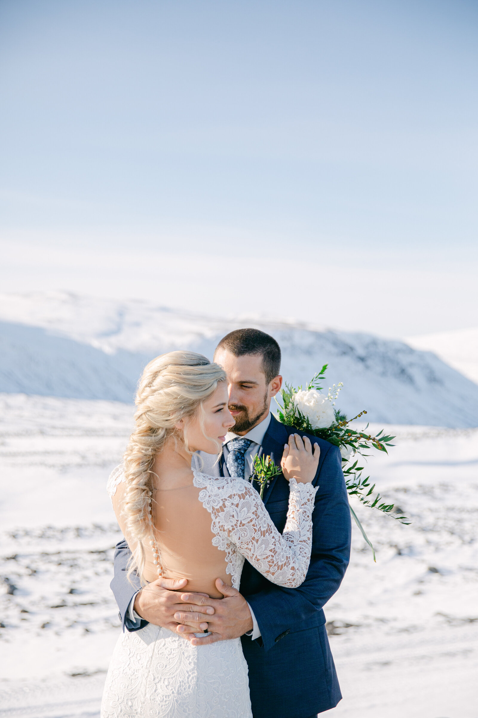 bride and groom face each other in iceland terrain with snow and rock all around them