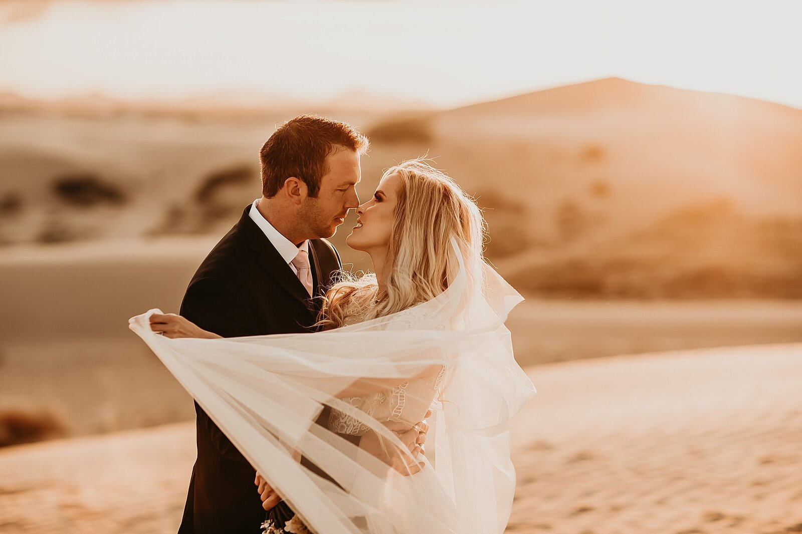 Bride and Groom Kissing in Warm Sun Outside
