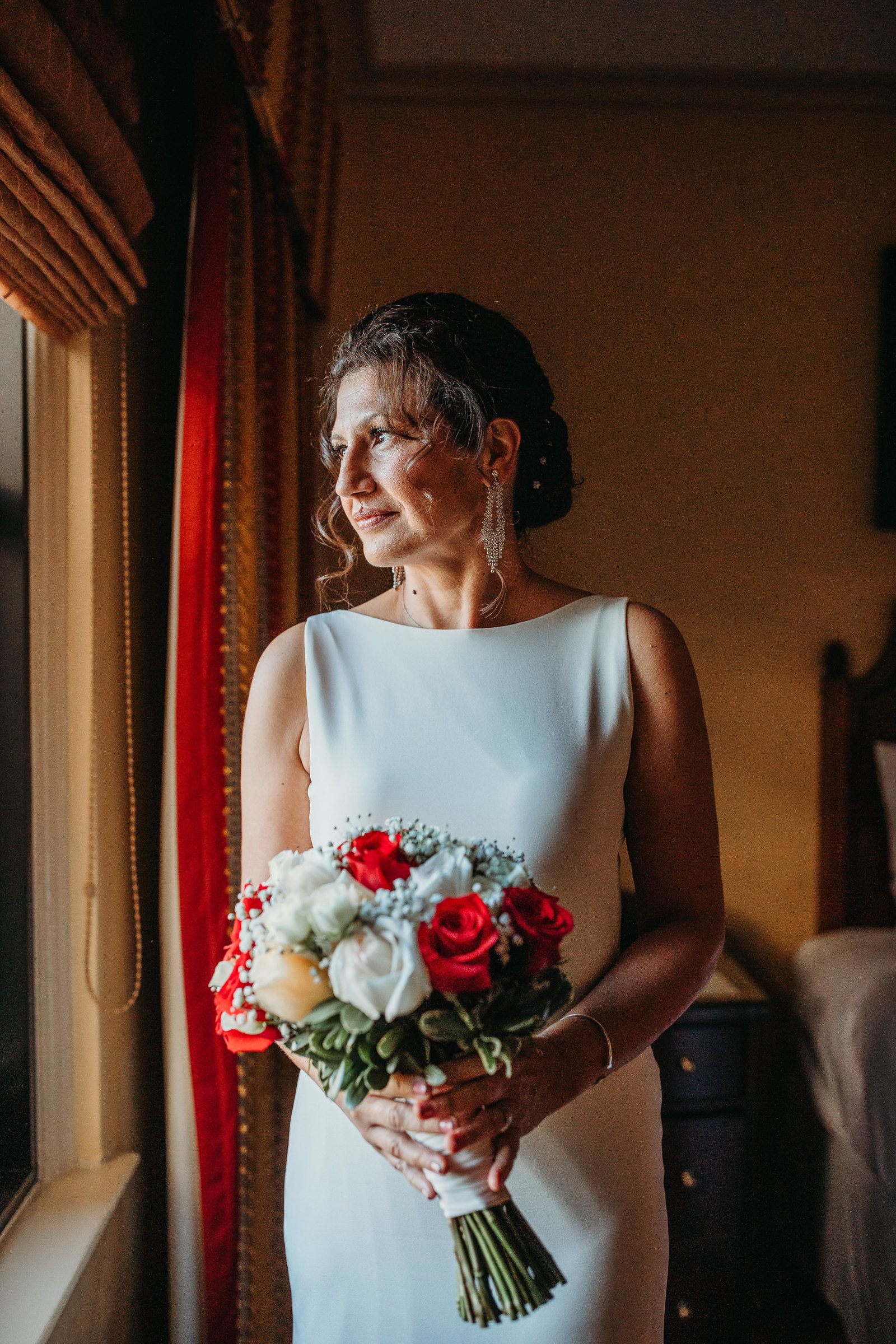 bride in elegant dress holds bouquet and gazes out hotel room window in boston ma
