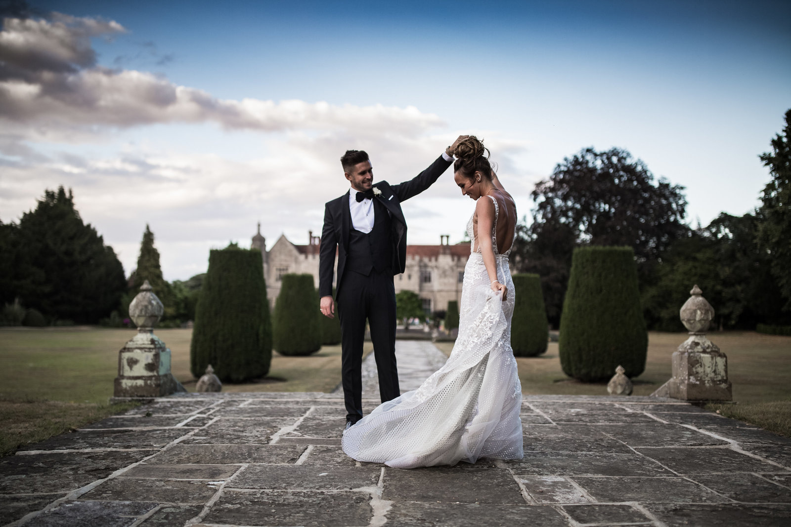 A groom stands on top of some steps and twirls his Bride. Hengrave hall is in the background.