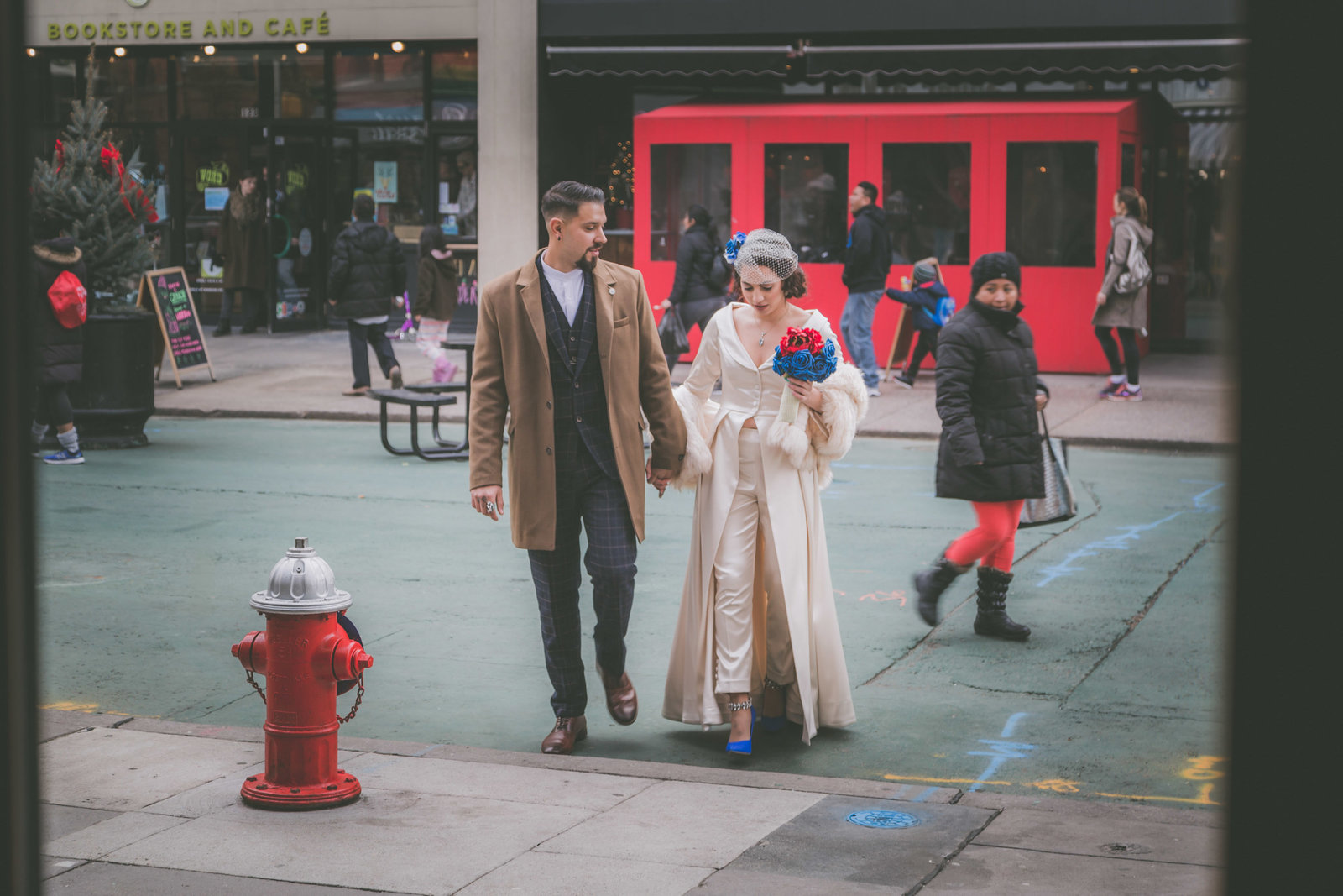 Bride and groom walk on Jersey City street.