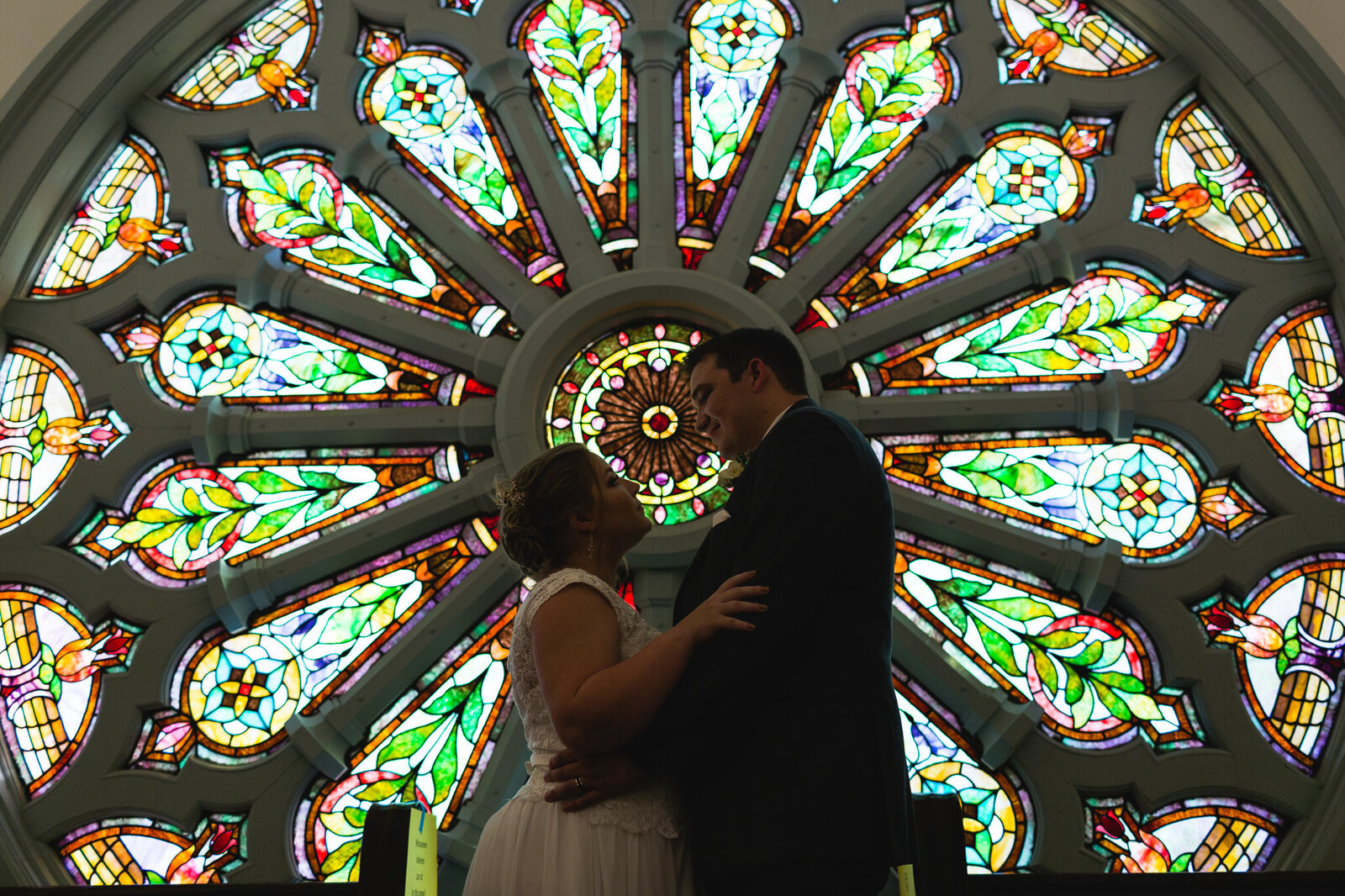 bride and groom portrait with stained glass window at church in ohio