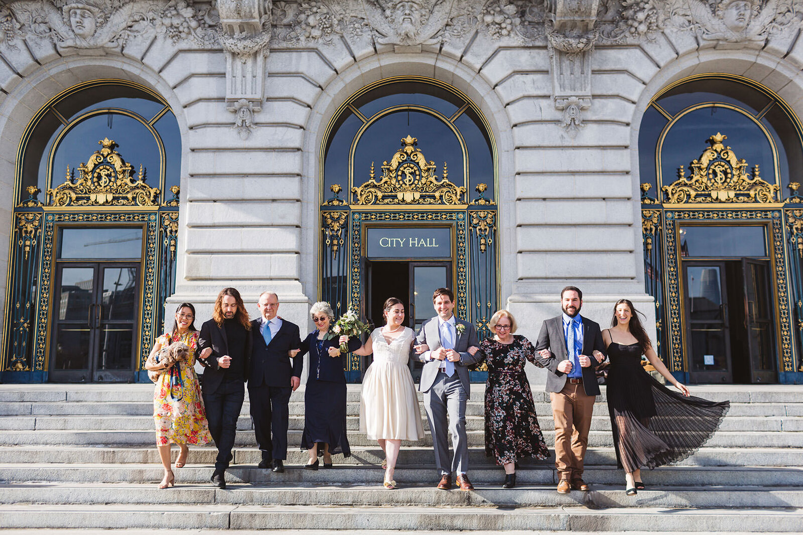 large wedding group walking down the steps of sf city hall, california