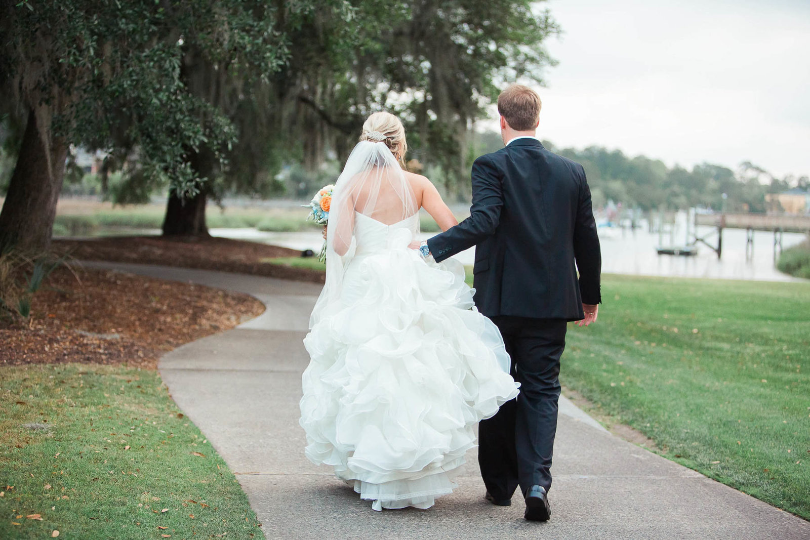 Bride and groom walk in field, Dunes West Golf and River Club, Mt Pleasant, South Carolina