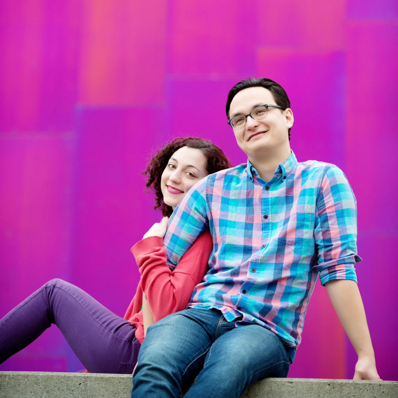 a man laughs as a woman leans on his arm in front of the pink museum of pop culture in seattle