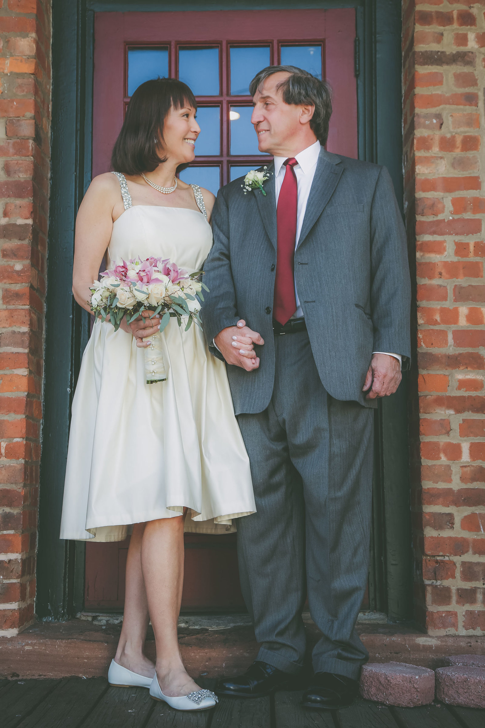 A New Jersey couple hold hands and look at each other against a doorway.