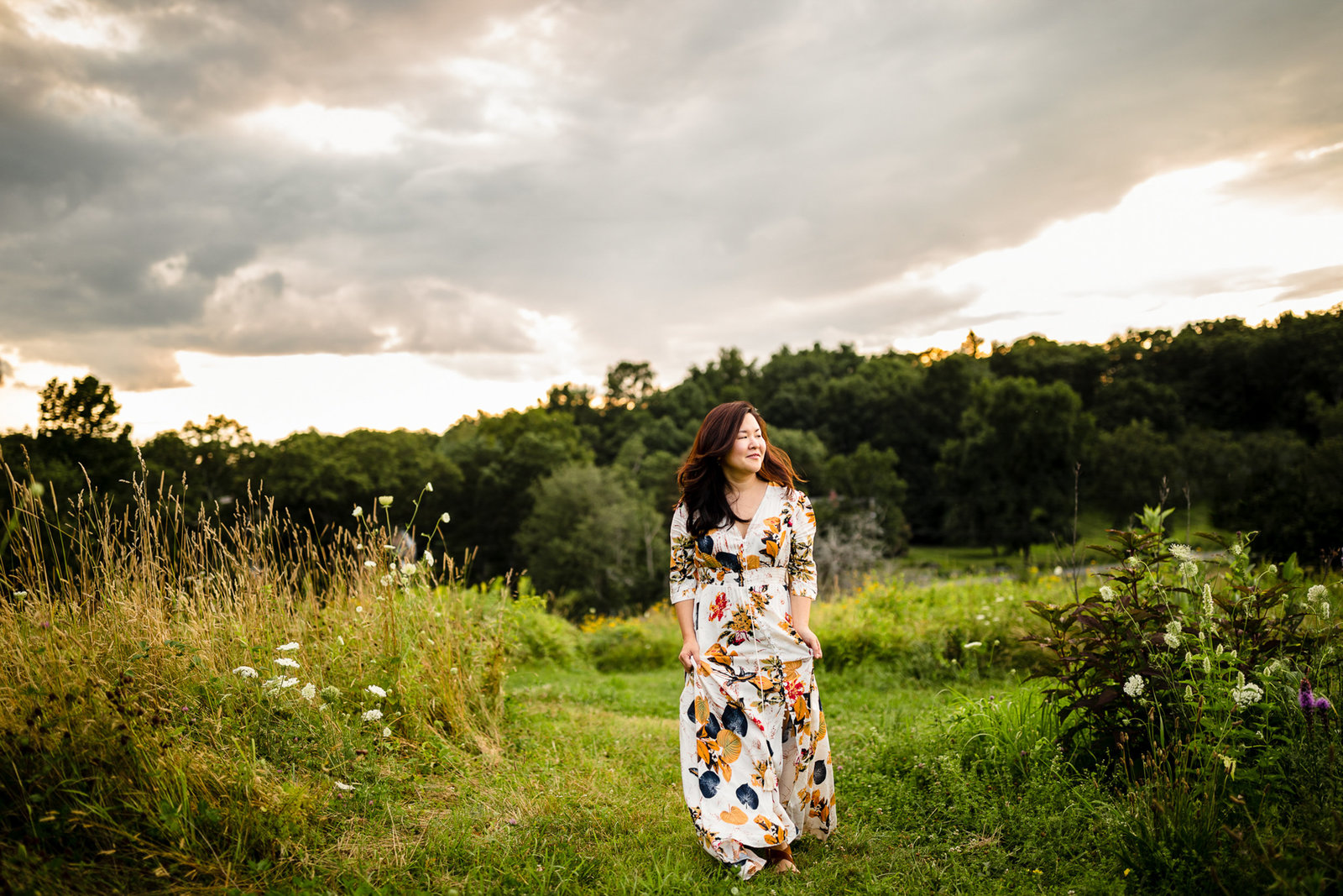 dark haired woman in white floral maxi dress walks in field in southborough ma