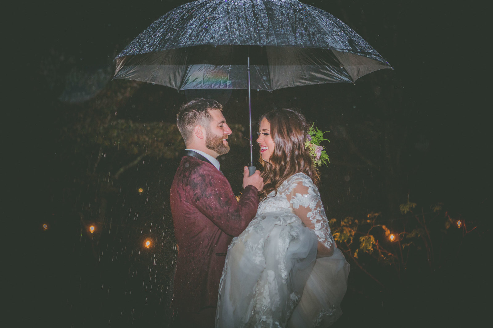 Groom holds umbrella for bride while raining at night.