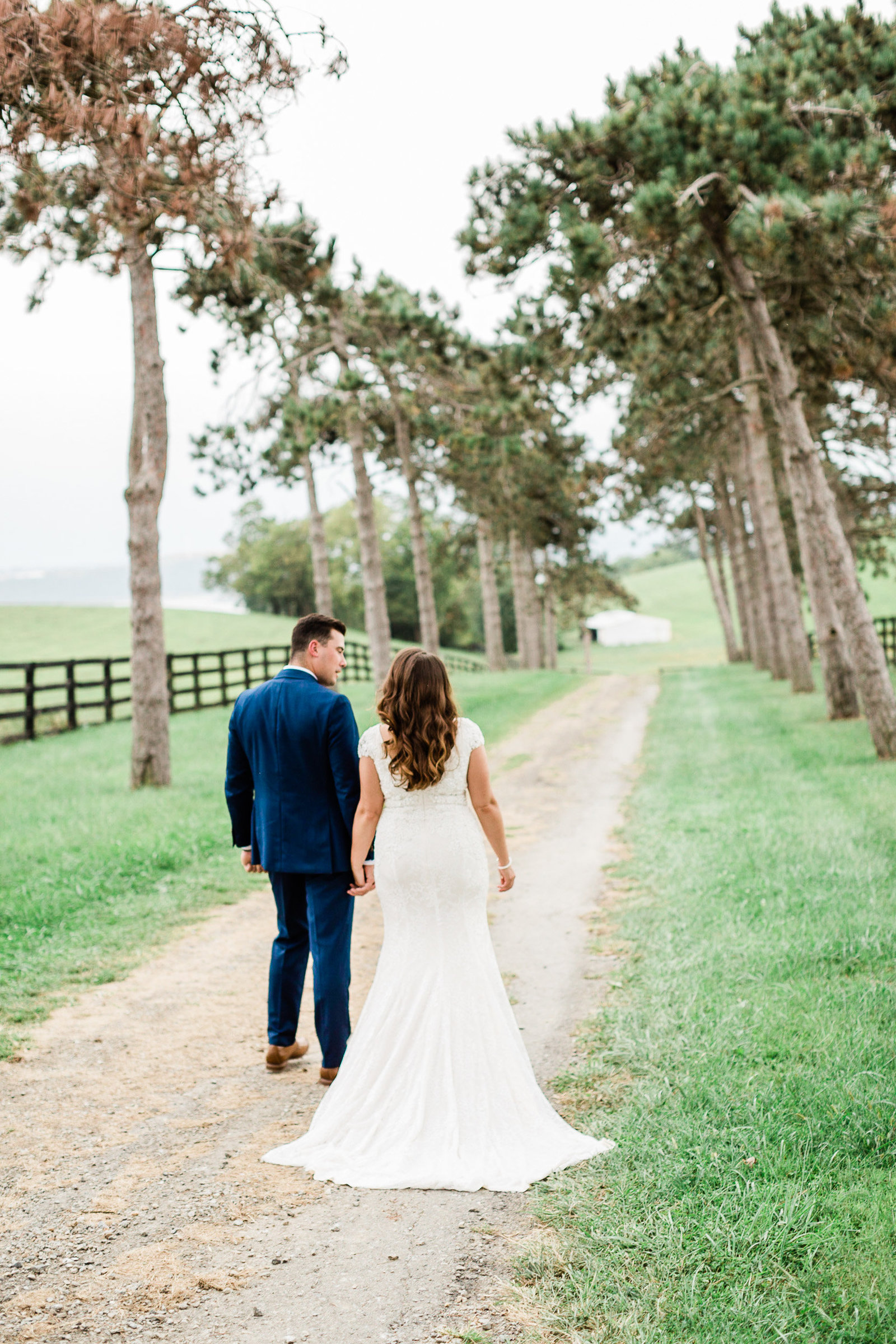 Bride and groom walk down a tree lined country road at Luxoumont Farm Pennsylvania