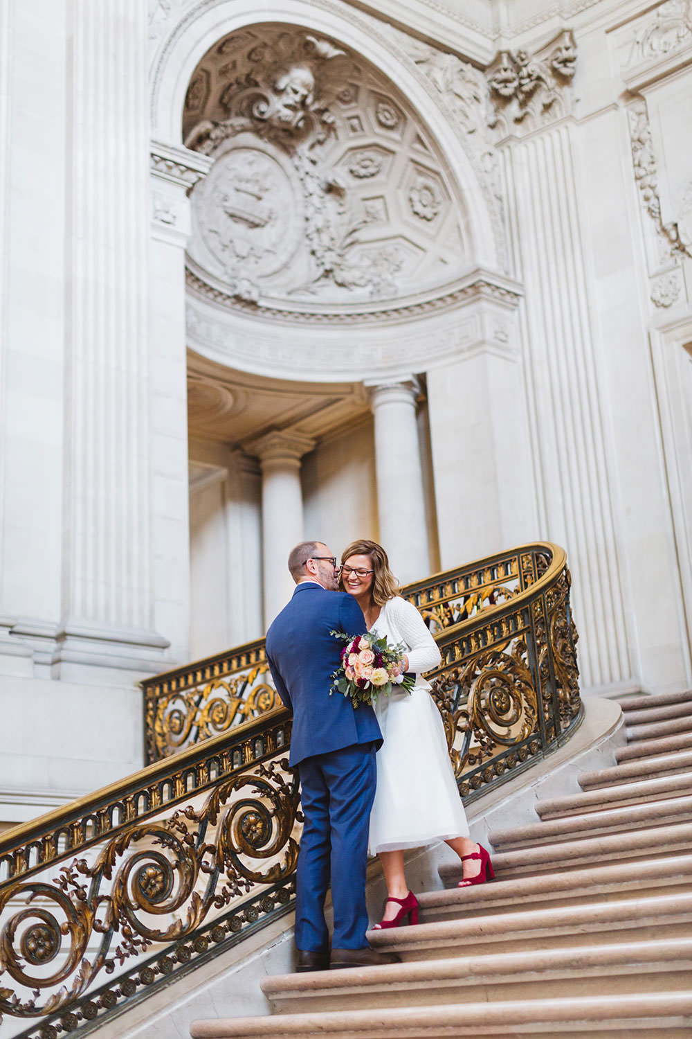 cute kisses on the grand staircase with bride in red shoes at city hall