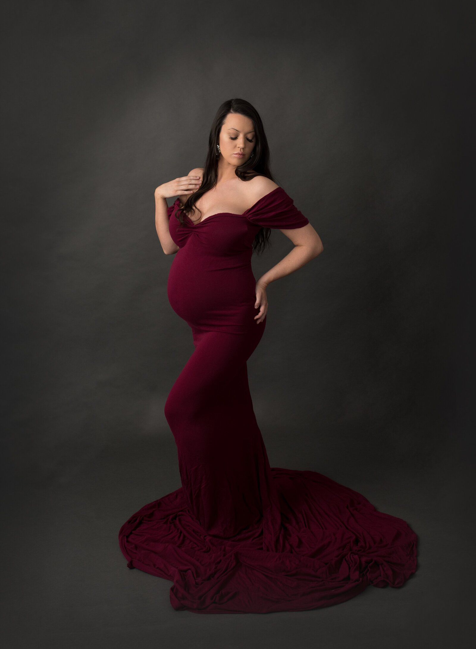 maternty photograph of a woman  wearing a wine coloured dress in a photography studio