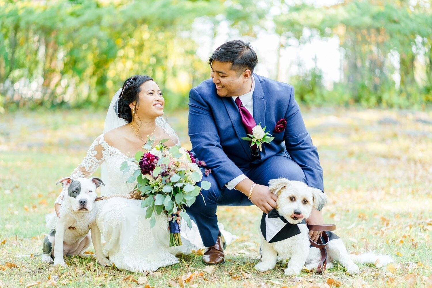 Bride and groom with colorful bouquet bending down and smiling with their dogs
