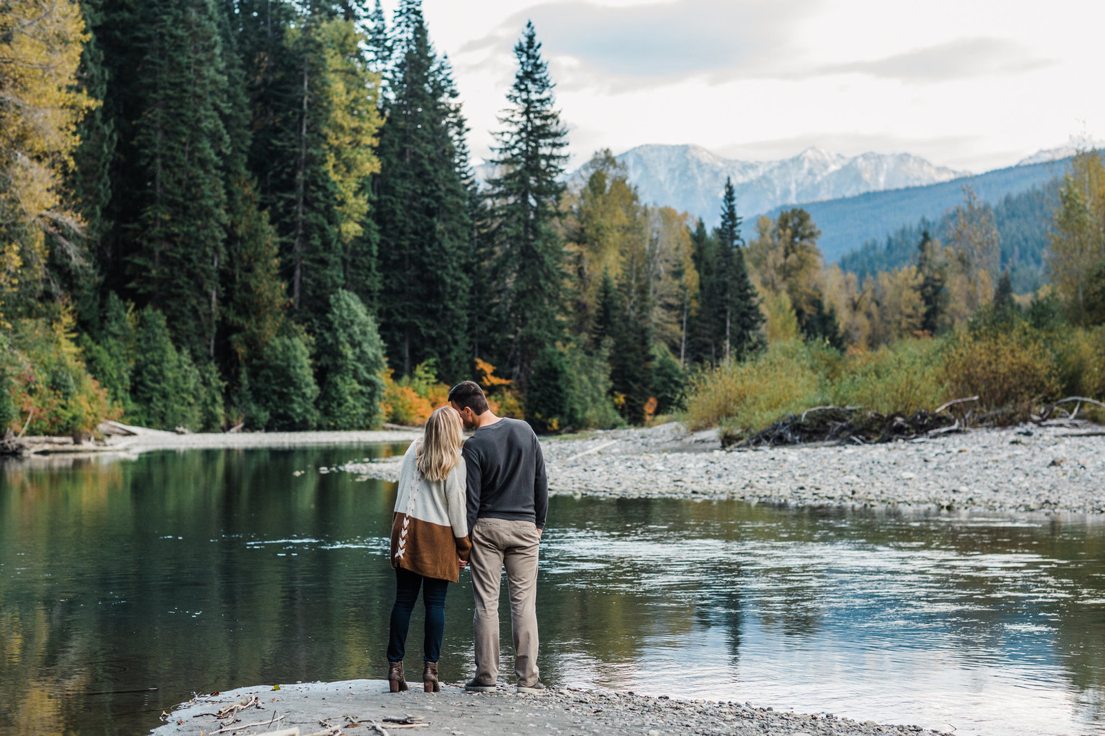 A couple kisses next to a river in Leavenworth during their adventure engagement session with PNW mountain elopement photographer amy galbraith