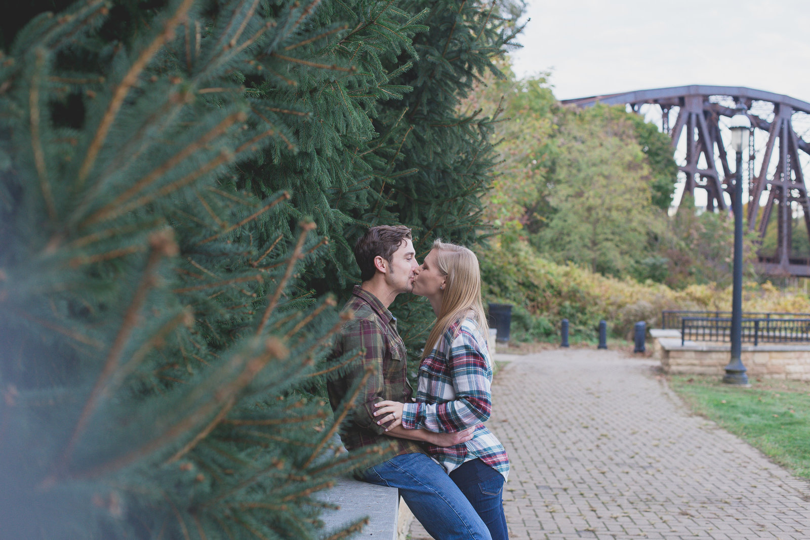 engaged_couple_kiss_among_pine_trees_in_park