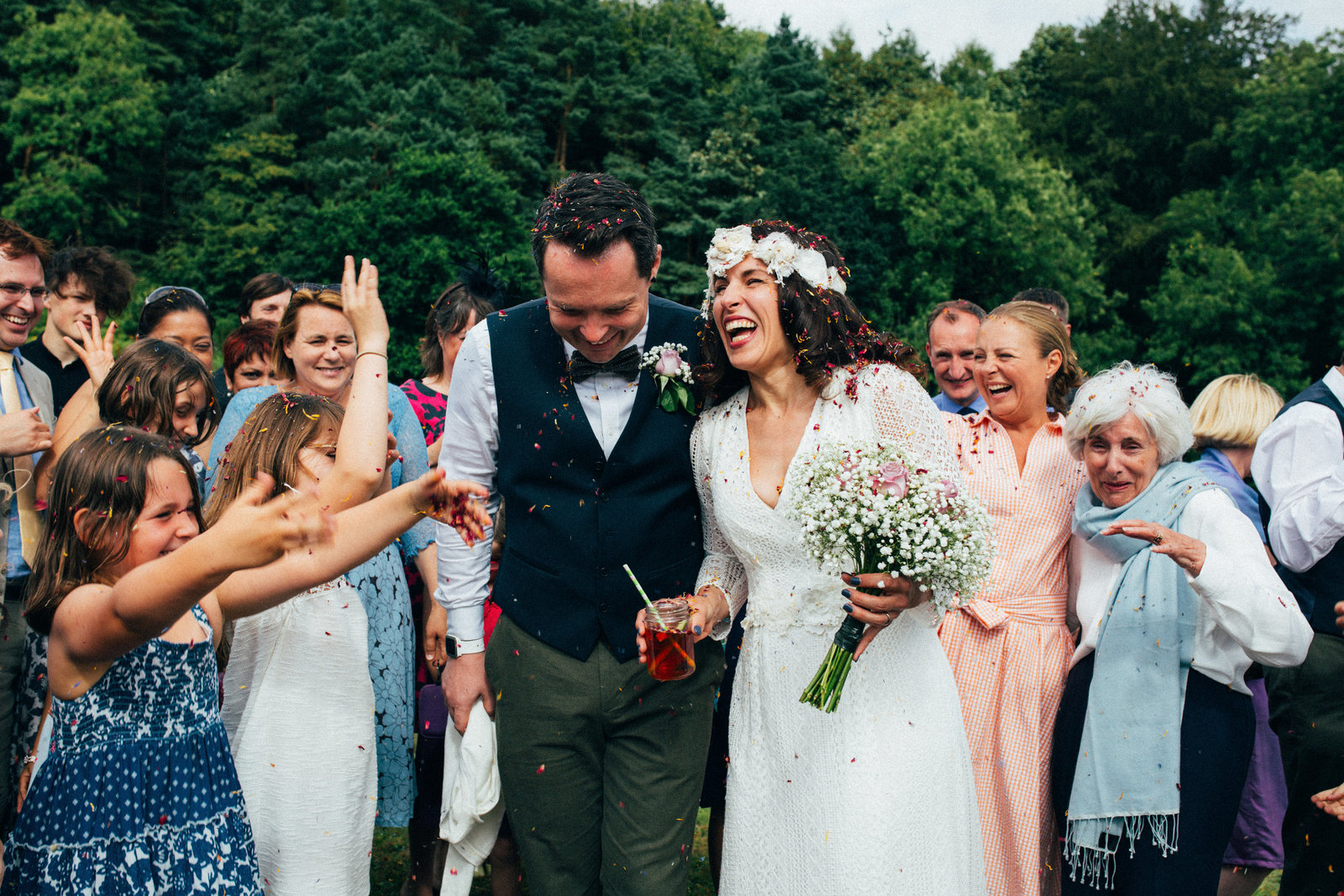 Bride and groom laughing and cuddling during their confetti throw at The Keeper and The Dell in Norwich