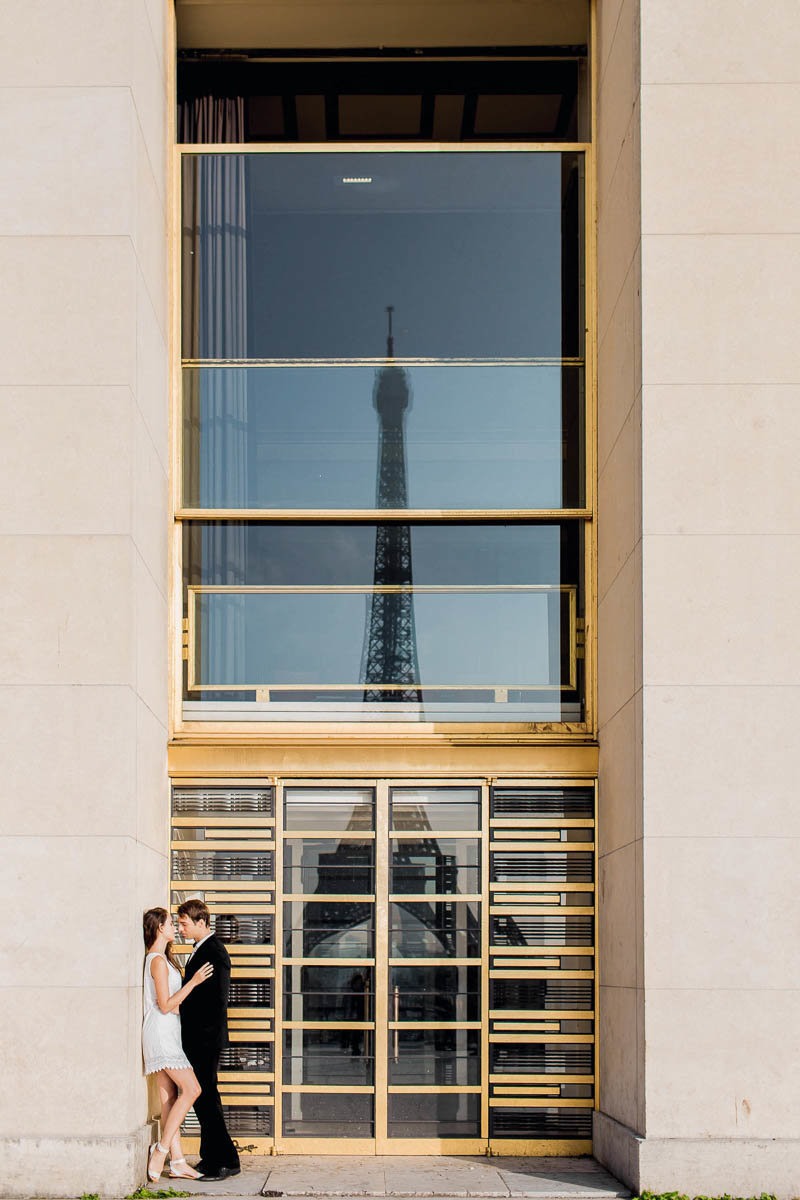 Bride and groom snuggle with the Eiffel Tower reflected in the glass, Paris, France