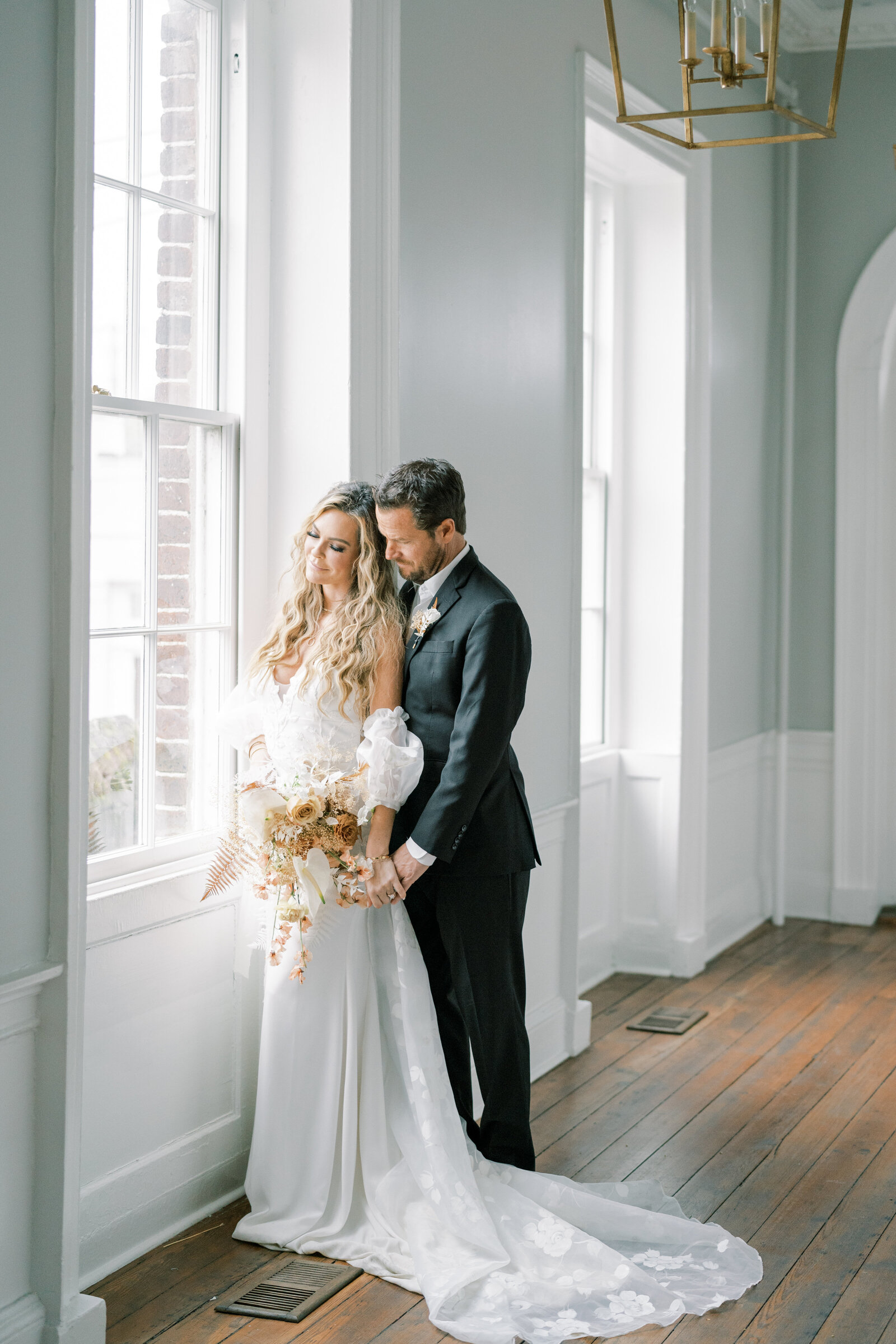 bride and groom standing at window  holding hands and looking outside at the gadsden house in charleston south carolina