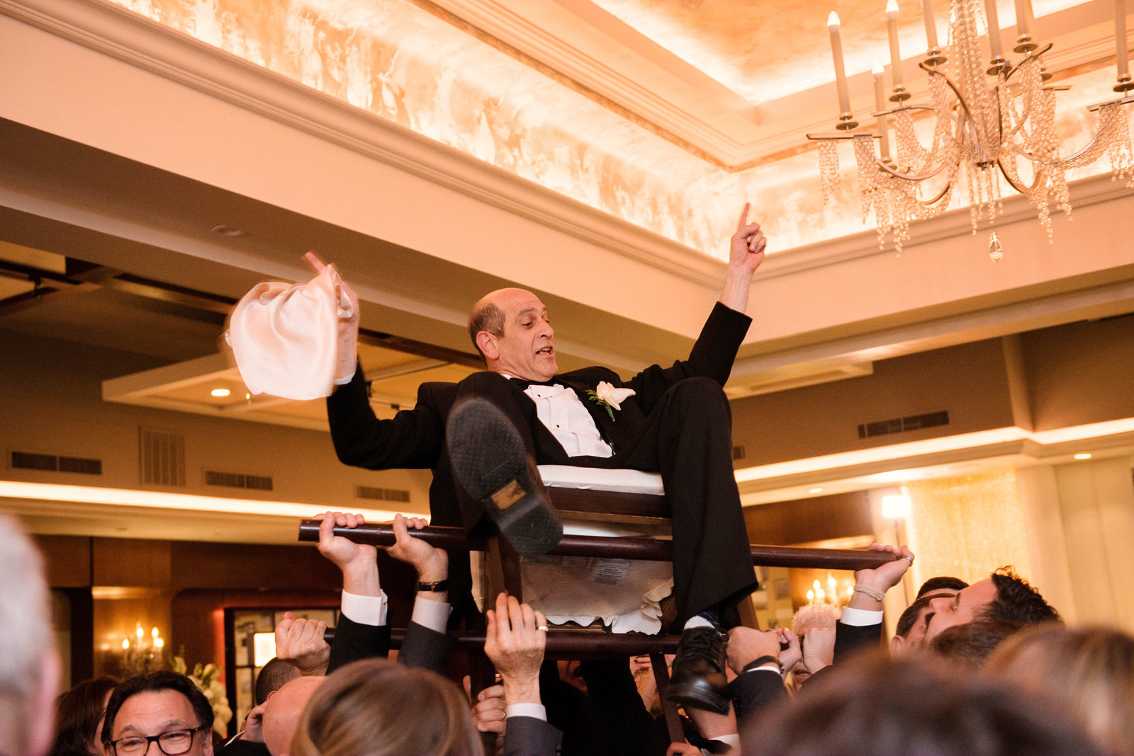 Father of the bride on the chair during the Hora
