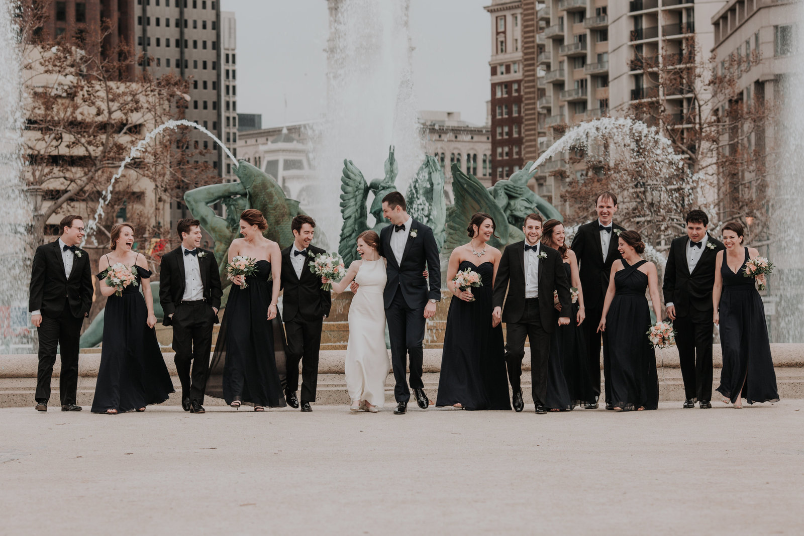 wedding party portrait in front of a fountain outside the logan hotel in philadelphia