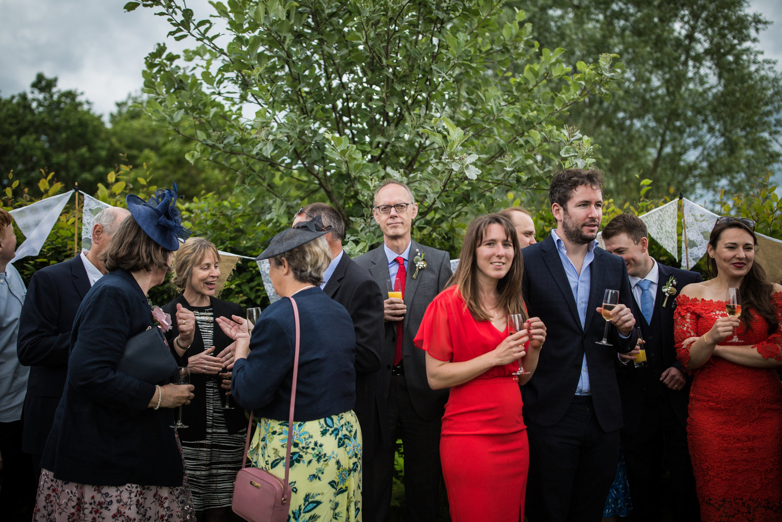 Amongst the happy faces and chatter at a wedding the grooms father is stood tall and staring with a blank face at the Norfolk photographer.