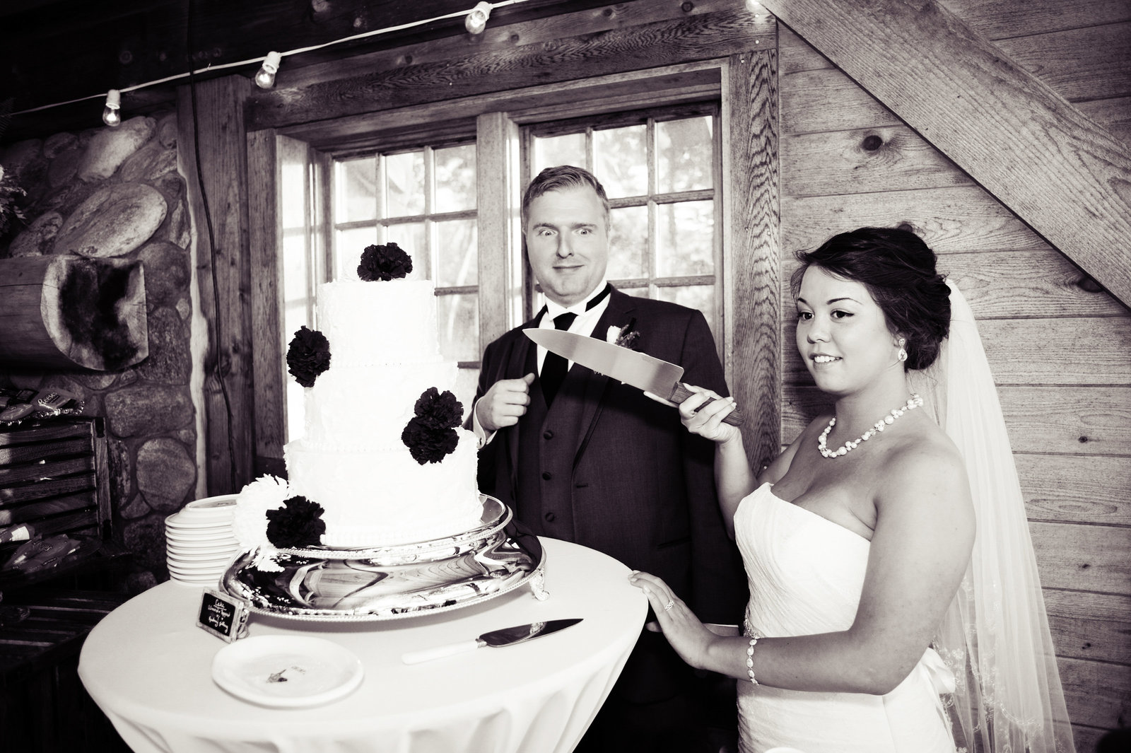 bride holds cake cutting knife to groom