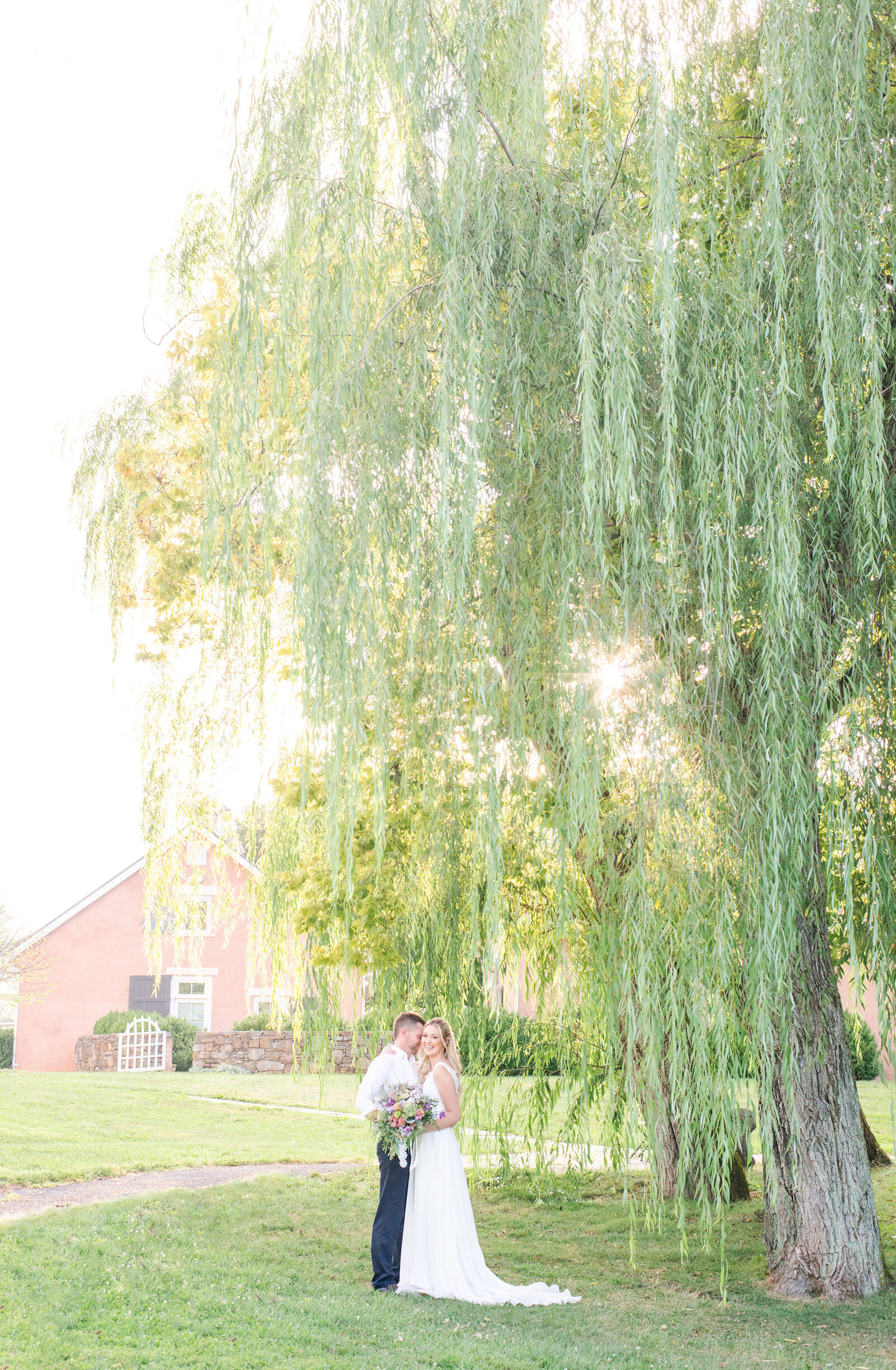 Bride and groom embracing under a weeping willow tree